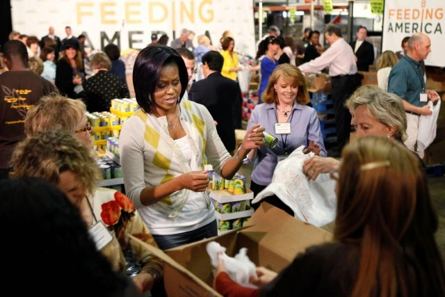 First lady Michelle Obama waits for her turn to get a plastic bag as she helps pack non-perishable food items along with congressional spouses and volunteers, at the Capital Area Food Bank, Wednesday, April 29, 2009, in Washington.    (AP Photo/Manuel Balce Ceneta)