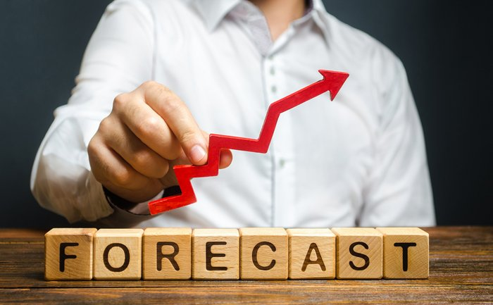 Man holds red arrow up over word Forecast. A budget surplus, prosperous economy or company. Prediction of profit growth, value of assets and market conditions. Increase income and earnings.