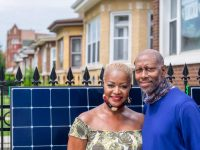 Debra and Greg Earl in front of their Chicago home with one of the solar panels to be installed on their roof.